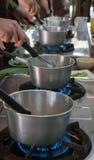 Pots d'acier inoxydable sur des brûleurs à gaz Photos stock