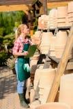 Pots d'argile de contrôle de femme de jardinerie Photographie stock