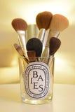 Pots de bougie de Diptyque réutilisés comme récipient de maquillage Photo libre de droits