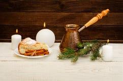 Pots de café, de brindille de sapin, de tarte aux pommes, de bâtons de cannelle et de bougies sur le fond en bois Image libre de droits
