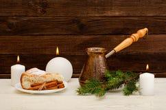 Pots de café, de brindille de sapin, de tarte aux pommes, de bâtons de cannelle et de bougies sur le fond en bois Photographie stock