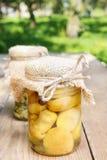 Pots de conserves sur la table en bois dans le jardin Image stock