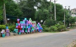 Pots de fleur colorés de ciment empilés du côté de la route Images libres de droits