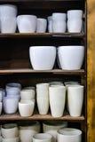 Pots de fleur vides élégants sur l'étagère en bois d'intérieur dans la boutique Photo libre de droits