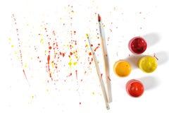 Pots de gouache et pinceaux sur un fond blanc avec le jet coloré dans la vue supérieure Photo libre de droits