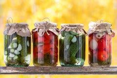 Pots de légumes marinés : concombres, tomates sur un shel en bois Image stock