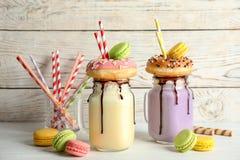 Pots de maçon avec des laits de poule et des macarons délicieux photographie stock