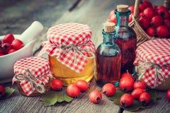Pots de miel, bouteilles de teinture et mortier des baies d'aubépine Photographie stock