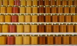 Pots de miel sur des étagères Images libres de droits