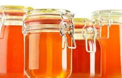 Pots de miel sur le blanc Images stock
