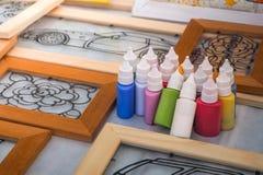 Pots de peinture sur la table avec des cadres en verre souillé Image libre de droits