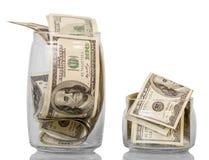 Pots en verre avec 100 billets de banque de dollar US d'isolement sur le blanc Photographie stock libre de droits