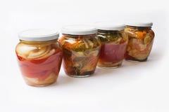 Pots en verre avec de la salade végétale différente d'isolement sur le fond blanc Images stock