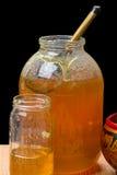 Pots en verre avec du miel et une cuillère en bois Photographie stock libre de droits