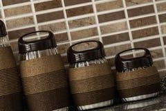 Pots en verre décoratifs enveloppés par corde sur le fond de Brown Images stock