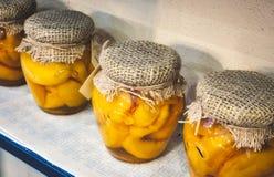 Pots en verre de pêches coupées en tranches couvertes de toile à sac et attachées avec de la ficelle photo libre de droits