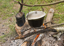Pots of food over a campfire Stock Image