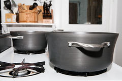 Pots on a Gas Stove. Pots for cooking on a gas stove in a kitchen with utensils in the background Royalty Free Stock Photography