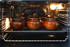 Pots in an oven. Five clay pots with a cover in an oven stock images