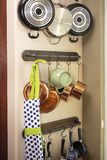 Pots and pans hanging on a kitchen wall to save space Stock Images