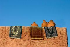 Pots and rugs drying in sun. Against blue sky Stock Images
