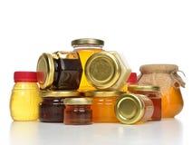 Pots savoureux doux de crème de confiture et de miel en composition en rangée avec Images libres de droits