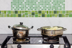 Pots and steaming pot. On the stove royalty free stock images
