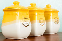 Pots of tea, coffee and sugar, yellow-white color on a white bac Royalty Free Stock Image