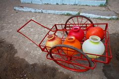 Pots and a vehicle for carrying water from far. Royalty Free Stock Images