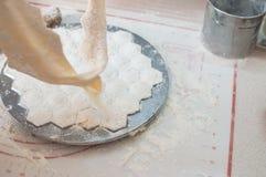 Potstickers faits maison faisant cuire la forme avec le pelmeni cru se tenant sur la table Cuisson de Pelmeni Photos stock