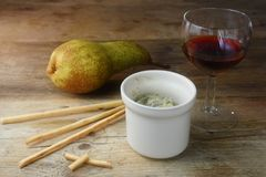 Potted blue stilton cheese in a ceramic jar, port wine, pear and Stock Image
