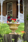 Potted Flowers in Front of an Old Nebraska Home. Red geraniums in an old stone pot sitting in front of a peaceful Nebraska home Stock Photo