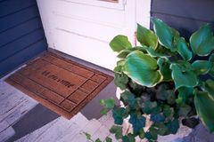 Potted plant alongside a Welcome mat. At a white wooden front door as a greeting to visitors Stock Image