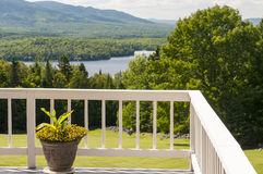 Potted plant on deck. Outdoor deck and pretty potted flower overlooking a scenic lake and mountain.  Moosehead Lake, Greenville, Maine Royalty Free Stock Photo
