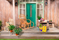 Potted plants and rocking chair on porch. With gardening tools Stock Image
