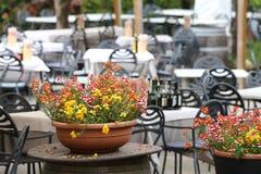 potten van bloemen op de lijsten in de bar in de open lucht Stock Afbeelding