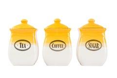 Potten van thee, koffie en suiker, geel-witte kleur op witte bac stock foto's