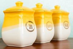 Potten van thee, koffie en suiker, geel-witte kleur op witte bac royalty-vrije stock afbeelding