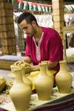 Pottenbakker artisanaal in nationale kleren in het paviljoen van Turkije binnen stock foto