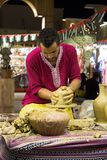 Pottenbakker artisanaal in nationale kleren in het paviljoen van Turkije binnen royalty-vrije stock afbeeldingen