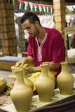 Pottenbakker artisanaal in nationale kleren in het paviljoen van Turkije binnen stock foto's