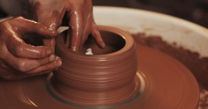 Pottenbakker die een kleipot cre?ren Workshop van klei Handen die aan aardewerkwiel werken, die een kleipot vormen De rode klei,  stock videobeelden
