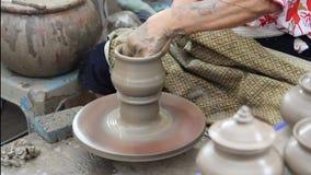 Pottenbakkershanden die in klei op aardewerkwiel maken stock video