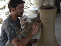 Potter. Karachi, Pakistan - May 8, 2011: Potter is designing and molding a vase on a pottery wheel at Karachi, Pakistan Stock Images
