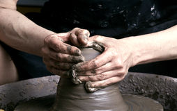 Potter. Hands of a potter, creating an earthen jar on the circle royalty free stock photo