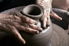 Potter. Hands of a potter, creating an earthen jar on the circle Royalty Free Stock Photography
