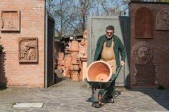 Potter carrying a jar. With a wheelbarrow Stock Image