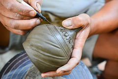 Potter carving pottery. Potter using knife to make tracery on pottery Royalty Free Stock Photography