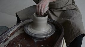 Potter Creates the Product on a Potter`s Wheel. on the Potter`s Lathe Spinning Pottery. stock footage