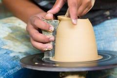 Potter creating clay bowl on turning wheel Stock Photo